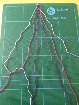 Pase el extremo del hilo lila sobre el hilo de color rosa para hacer un lazo y tire de la parte superior para crear un nudo. Repite de nuevo para crear un nudo doble en el mismo hilo.