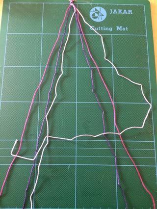 Repita el mismo procedimiento desde el lado derecho. A partir de la lila pálido (a la derecha) del hilo, crea un invertida'L' shape across the other threads and feed the end under the pink thread and pull