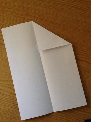 Desdoble ella .. Coge una esquina y crea un triángulo asegurándose de que's edge is on the line of fold you just made in step 1