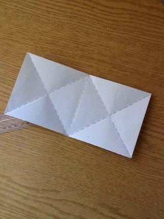 Cuando desplegado usted debe tener un pedazo de la forma de un gran rectángulo dividido en dos cuadrados iguales .. Cada cuadrado se ideó en 4 triángulos de papel ..