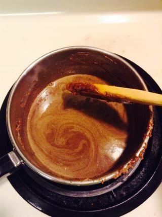 Baja del quemador, y añadir el azúcar y la mezcla de chocolate caliente. Mezclar hasta que se mezclen. Añadir media taza de la leche y mezclar hasta que esté más o menos licuado.