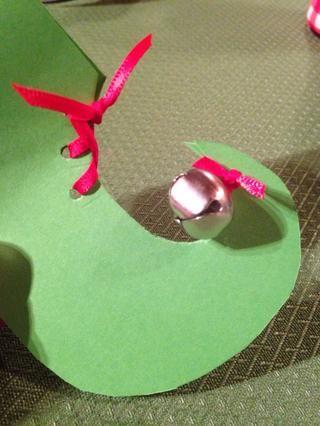 Usando cinta, atar el cascabel en la punta del zapato, anudando para asegurar.