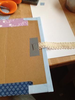 Papel pegamento en la caja de cartón con la barra de pegamento. Añadir la cinta, usé cinta adhesiva. Cortar una pequeña ranura y pasar la cinta a través de la parte delantera.