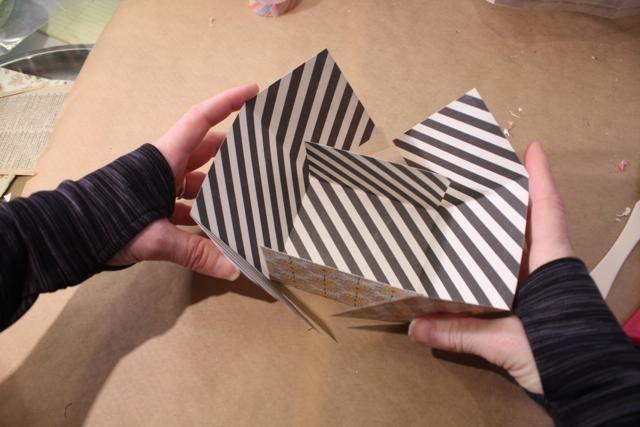 Voltear en las dos solapas tiro y doblar las largas aletas como se muestra para crear la forma de la caja