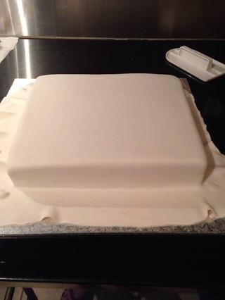 Sumerja un cepillo en un poco de agua y cubrir todo el pastel asegurándose de no demasiada agua y luego Cubra el pastel con fondant