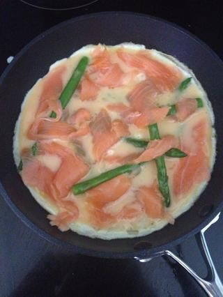 Lágrima de tiras del salmón ahumado y tirarlos en los frittata de cocina. Doesn't need to be neat. Leave the frittata to cook like this for one or two minutes. Don't let it burn underneath.