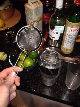 Deseche el hielo de la copa de martini y la doble presión de su brebaje en el uso de un filtro de Hawthorne (el que tiene la primavera) y el colador fino.