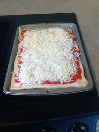 Espolvorear el queso mozzarella en la parte superior de la pizza hasta que se distribuye uniformemente a través de los bordes de la masa.