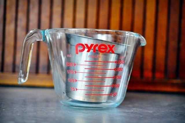 Coloque el té de manzanilla en un colador de té y coloque el filtro en un 1 taza taza de medir de vidrio.