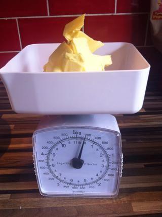 Mida 7 oz / 200 gramos de mantequilla softned.