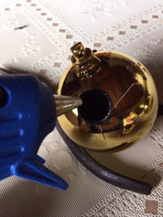 Ejecutar cuidadosamente una línea de pegamento caliente en el agujero en el interior, donde se le inserta el adorno más pequeño.