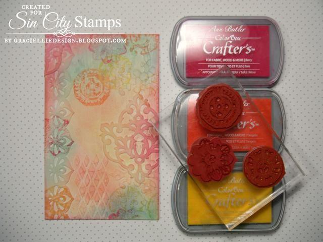 Uso de tintas multisuperficie en Berry, Tangelo y sol me estampadas algunas imágenes Rossette de Sellos Sin City en el lienzo de color.