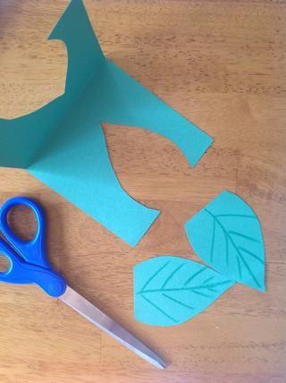Corte dos hojas de papel de construcción verde. Use crayones para dibujar líneas en las hojas para que se vean reales.
