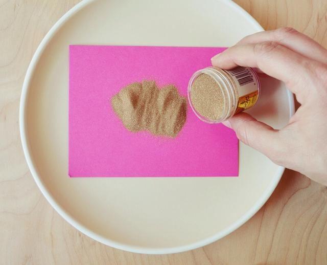 Coloque su tarjeta de nota en el plato y vierta generosamente su polvo que realza para cubrir la superficie de la tinta de estampación fresco. Deje reposar durante 10 segundos o menos.