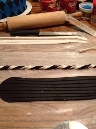 Estirar la pasta de azúcar más blanco y negro. Cortar en tiras de 1/2 pulg, colocarlos en pares, y girar juntos.