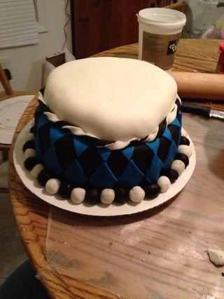 Aplicar la cadena fondant trenzado alrededor de la base de la capa Skullette. Enrolle las bolas de la pasta de azúcar blanco y negro y colocarlos alrededor de la base de la tarta.