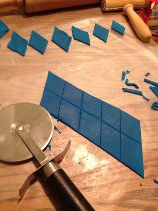 Estirar la pasta de azúcar azul. Utilice un cortador de pizza para cortar en grandes formas de diamante.