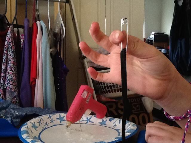 Pase el elástico a través de la clavija y cierre el pasador