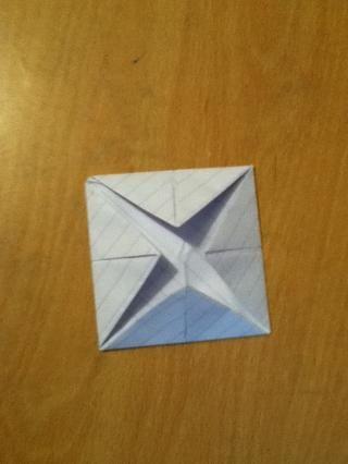 Dé la vuelta al papel y doblar todas las esquinas hacia el centro de la parte posterior del papel!