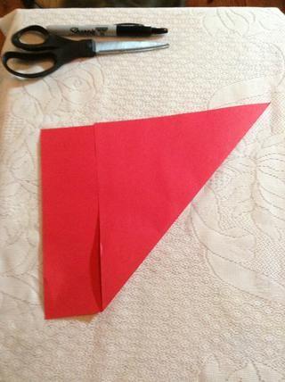 Doble la esquina superior izquierda o derecha en diagonal hacia abajo tanto como sea posible a la orilla opuesta del papel para hacer un triángulo.