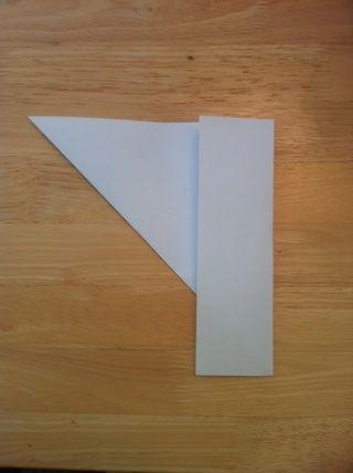 Darle la vuelta y doblar la pieza rectangular de largo hacia atrás sobre su triángulo.