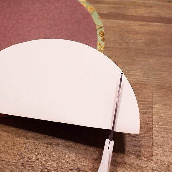 Cortar un círculo grande en cada uno de los 12 × 12 trabajos de artesanía de papel de tarjetas. Doble por la mitad y cortar alrededor de una pulgada de la parte inferior para crear el fondo plano de la calabaza.
