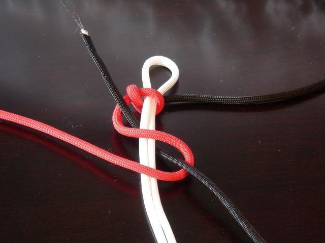 Repita la misma operación como antes, pero esta vez crear el bucle S desde el lado opuesto. Tire el cable negro a través y cinchar el nudo.