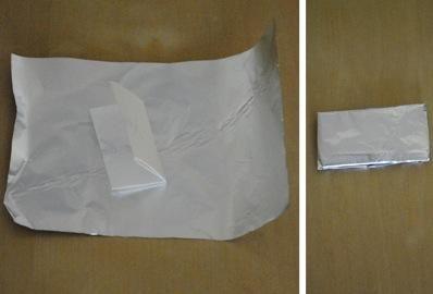 Mientras que la vela se está derritiendo, prepare su mensaje para ser colocado dentro de la vela. Doble la hoja de papel y envolver el papel de aluminio alrededor de él, cubriendo el papel completamente y apretado.