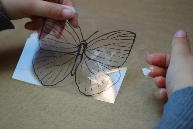Continuar a capa las cintas y colocar trozos de cinta al azar en todo el mariposa hasta que esté completamente cubierto.