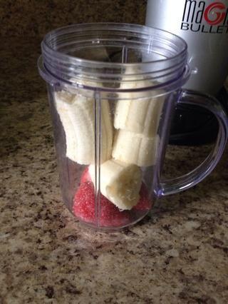 Ponga en 4 fresas (congeladas o frescas). Romper el plátano en trozos y ponerlo en también.