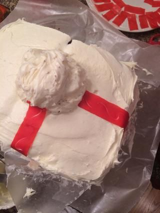 Coloque una cucharada colmada de helar en el centro de la torta. Entonces, yacía Fruit acumulativo de tiras que viene en forma de cruz de la zona central (como un regalo). Recorte en los extremos, cuando el paquete acumulativo llega al plato.