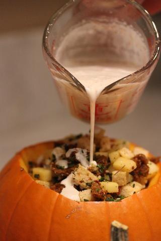Verter la crema y nuez moscada en la calabaza rellena, lentamente, dejando que se absorba en el pan y mezclar con otros ingredientes.