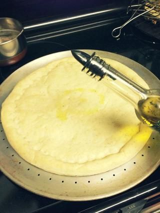 Rocíe un poco de aceite de oliva (o aceite de albahaca con sabor como el mío) sobre la masa de la pizza y se extendió con el dorso de una cuchara o un cepillo.