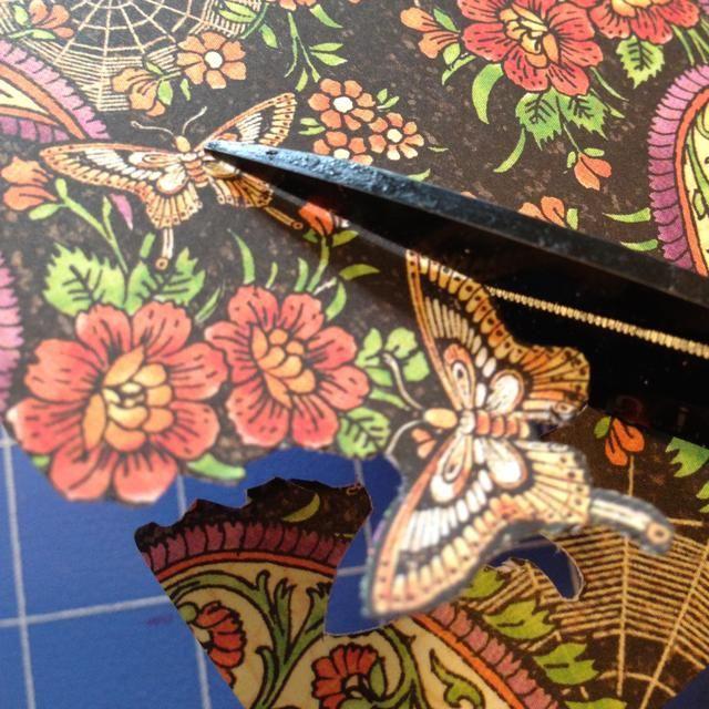 Fussy cortar algunas flores de color naranja y una mariposa, y cualquier otra cosa en el papel que desea dentro del tapetito.