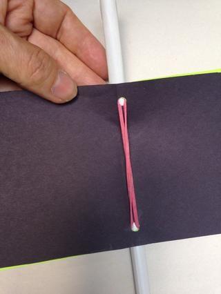Ahora estirar la banda elástica para el otro agujero. Empuje hacia abajo a través de todas las páginas y por el otro lado.