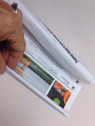 Estrechamente enrollar la página de la revista para hacer un palo.