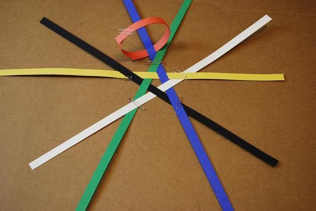 Deslice el lazo naranja de modo que la franja azul que está en la franja verde es a través del bucle. Manténgalo así el lazo naranja está tocando la punta de la estrella como se muestra arriba.