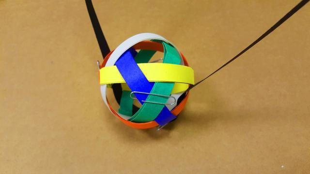 Antes de enrollar el fleje amarillo, tejerlo sobre el bucle blanco, bajo el bucle de azul, y sobre el bucle verde. Entonces la bobina al mismo tamaño que el bucle de naranja.