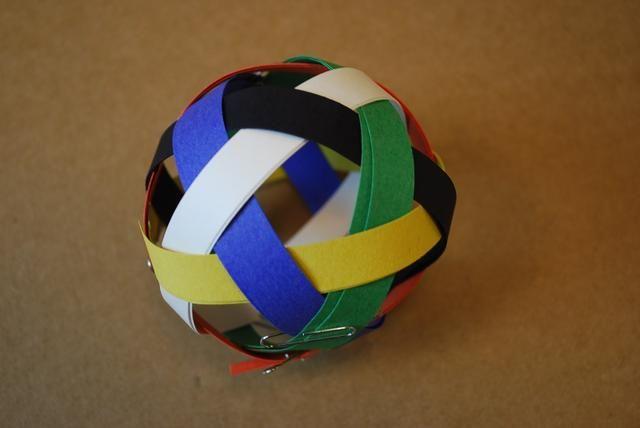 Para la tira de negro, tejer bajo el bucle de azul, blanco sobre el bucle, bajo el bucle verde, y sobre el bucle de color amarillo. a continuación, la bobina al mismo tamaño que el bucle de naranja. Luego sacar los clips de papel.