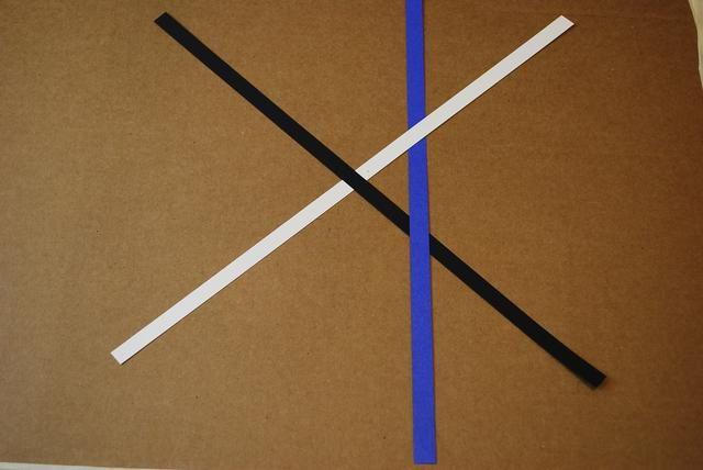 En el lado derecho de la X, deslice la franja azul bajo el blanco y negro sobre la tira.