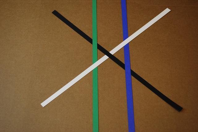 En el lado izquierdo de la X, deslice la tira verde sobre el negro y debajo de la tira blanco.