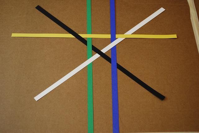 En el lado superior de la X, deslice una tira amarilla bajo el negro, el verde, bajo el azul, y sobre el blanco.