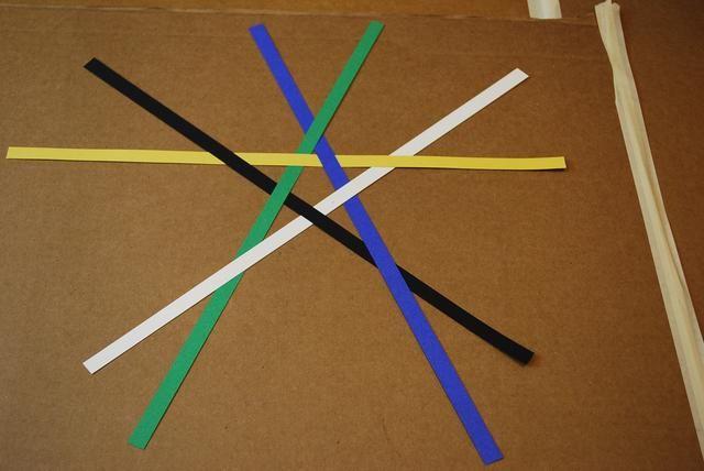 Mira la mitad superior de la estrella y cruzar con cuidado la tira verde sobre la franja azul para formar una forma de estrella en el centro de su patrón. Observe cada tira va sobre y debajo de la otra.