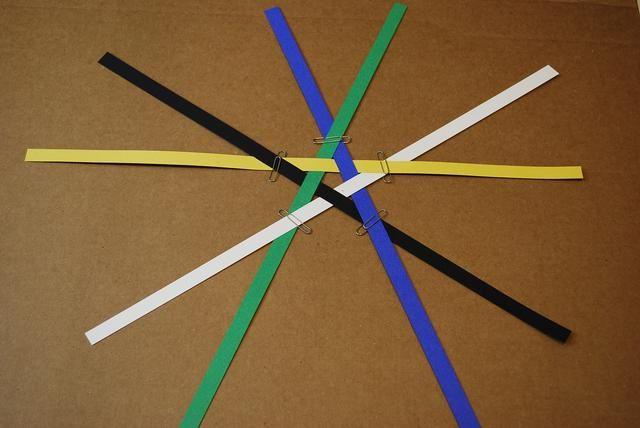 Coloque los clips de papel en el punto de cada estrella. Deslizando el patrón hasta el borde de la mesa puede ayudar a fijar el clip más fácil.