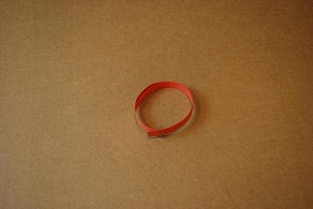 Tome la tira de naranja y la bobina al tamaño de toda su estrella y mantenerlo en su lugar con un clip de papel.