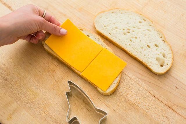 Añadir sus dos rebanada de queso para su pan. Asegúrese de obtener el pan que es el tiempo suficiente para adaptarse a su cortador de galletas de tiburón.