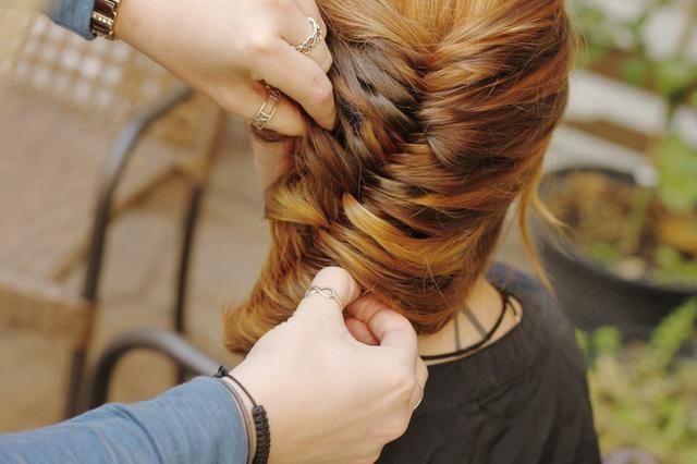 Ahora pellizque el exterior de varias trenzas y tire hacia fuera para dar un toque vivir-en y hacer que el cabello se vea más grueso. Pin secciones sueltas en su lugar, y rociarlo con spray para el cabello, según sea necesario.