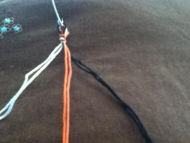Duplicar sus hilos y haga un nudo dejando un bucle. Utilice el pasador de seguridad para insertarse en una almohada u otra superficie de trabajo. Divida el hilo por el color. Mi hilo naranja es el centro / hilo invisible.