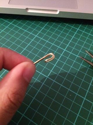 Usando los alicates de punta redonda, de unos 2 cm por el lado curvo del alambre, doblar hacia adentro sin bucle completamente. En una especie de forma de gancho.
