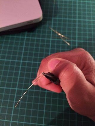 Usando sus alicates de punta redonda, envolver el alambre alrededor de la punta en aproximadamente 1 cm por el cable. Envolver la pieza alrededor de la parte inferior del bucle.